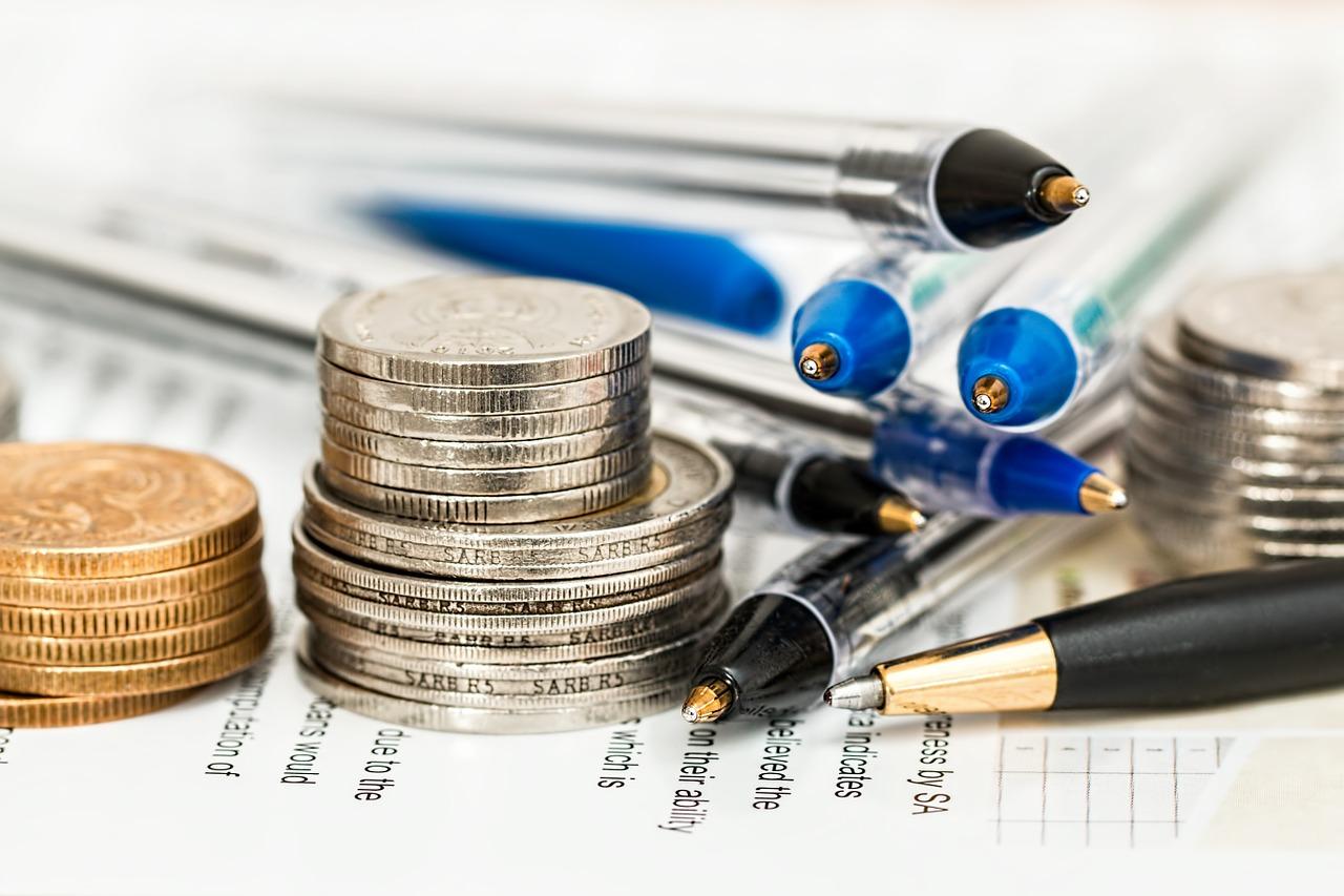 Mynt och pennor på ett papper