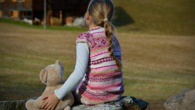 Ett barn som sitter med en nalle