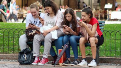 Unga tjejer som sitter på ett staket och använder sina mobiler