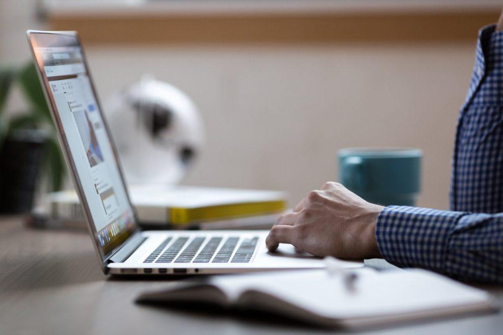 En person som sitter och skriver på en bärbar dator