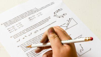 En hand håller en penna ovanför ett mattetest