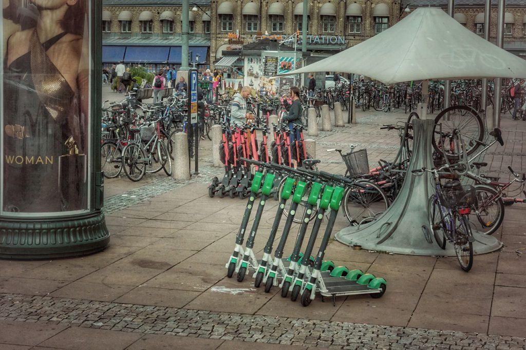 Gröna och röda elsparkcyklar som står på rad