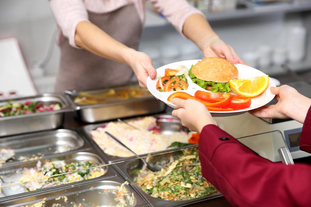 En elev får en tallrik med mat på av en som jobbar i skolköket.