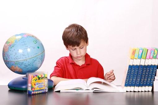 En pojke studerar bredvid en jordglob och massa böcker
