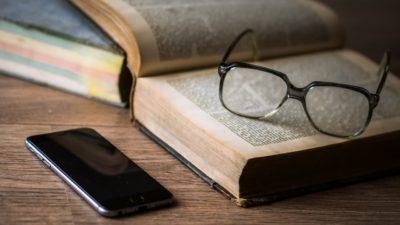 En telefon har lämnats kvar bredvid en uppslagen bok