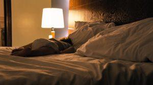 En nattlampa lyser på nattygsbordet bredvid en stor säng.
