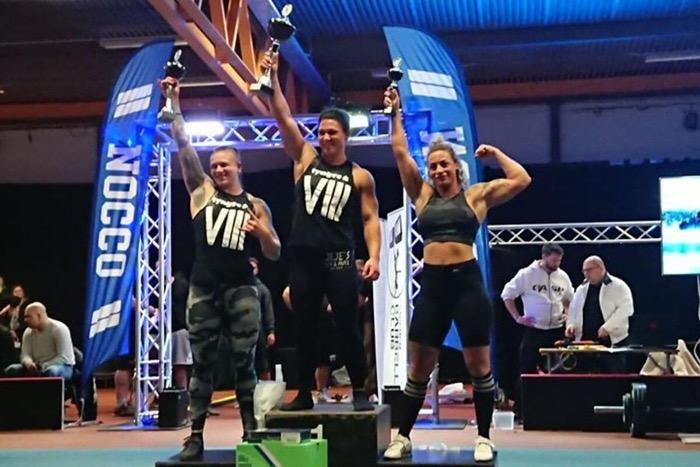 Martina står på medaljpodiet och lyfter upp en pokal i luften.