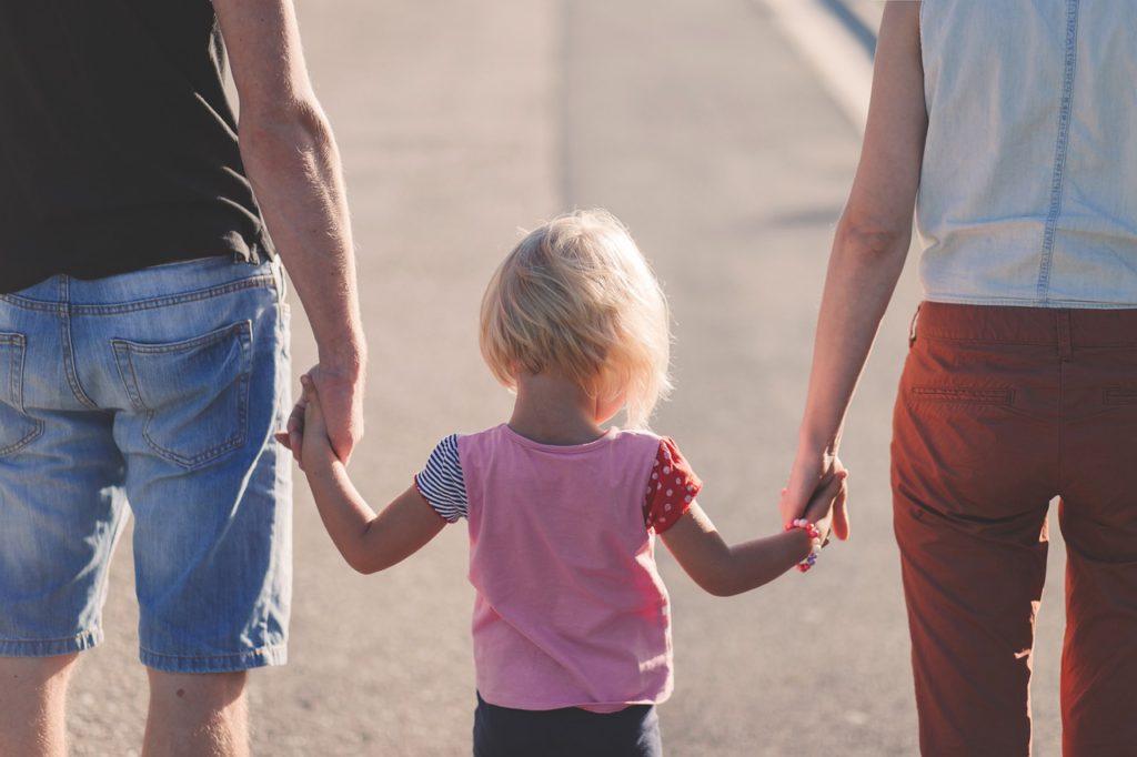 Ett barn som håller sina föräldrar i handen