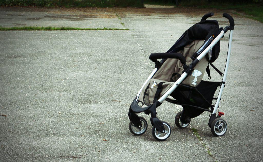 En tom barnvagn på en asfalterad väg.