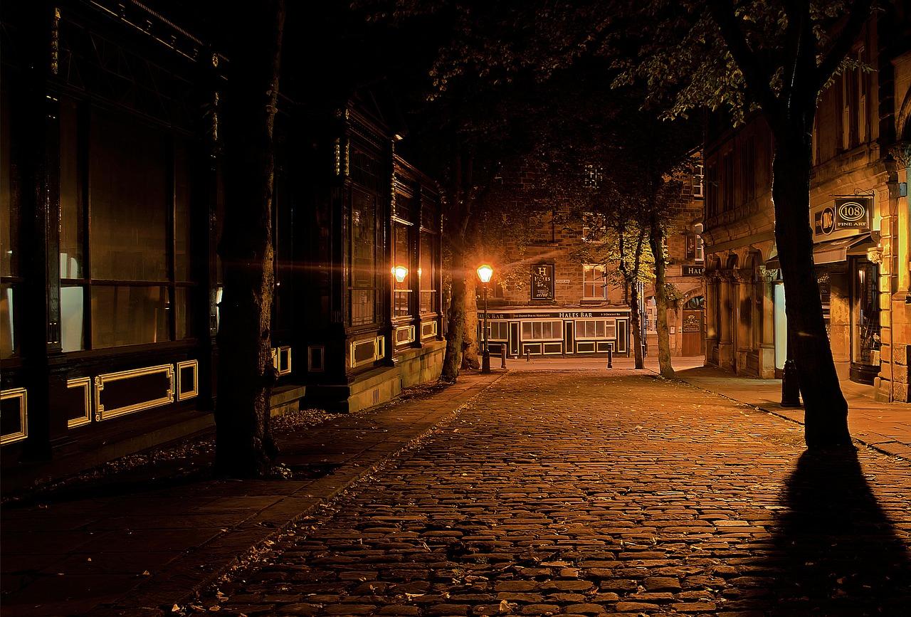 En mörk natt på en gata i stan. Det är en kullerstensgata med träd längs sidorna. Längre fram lyser några gatlampor.