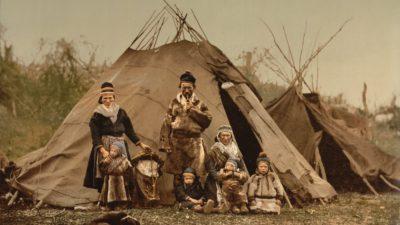 En grupp med samer, tre vuxna och fyra barn, uppställda framför en kåta, ett slags tält.