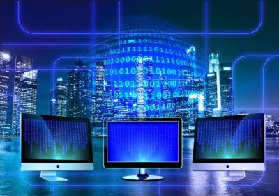 Datorer i blått ljus. I bakgrunden är det massa ettor och nollor