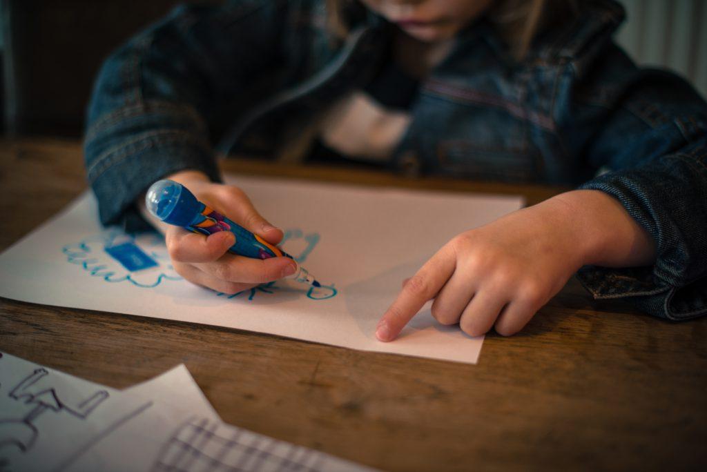 En flicka som ritar på ett papper.