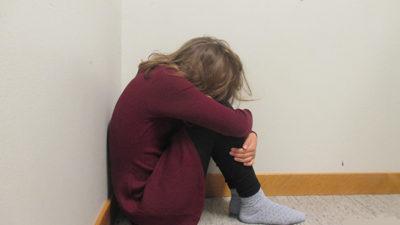Foto på elev som gömmer ansiktet i knät.