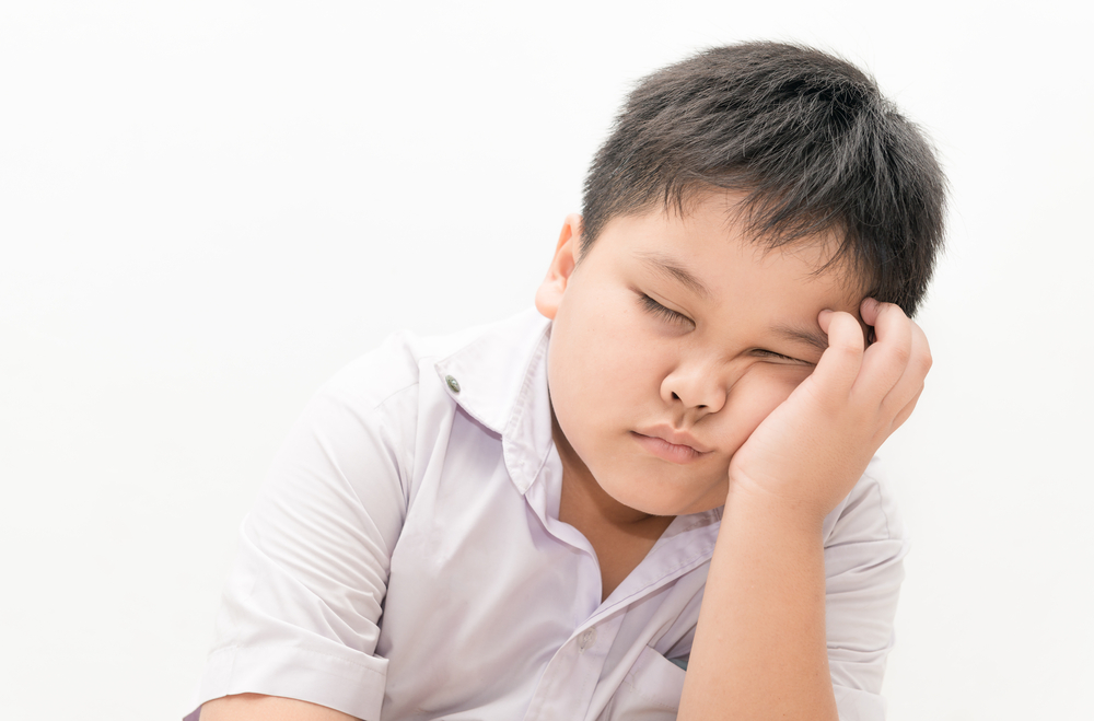 Ett barn sitter med huvudet i handen och sover.