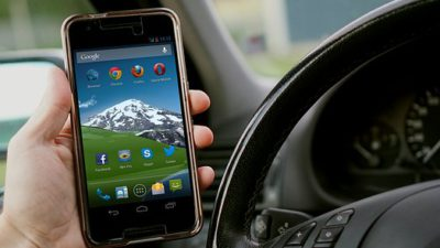 En hand håller i en telefon inne i en bil.
