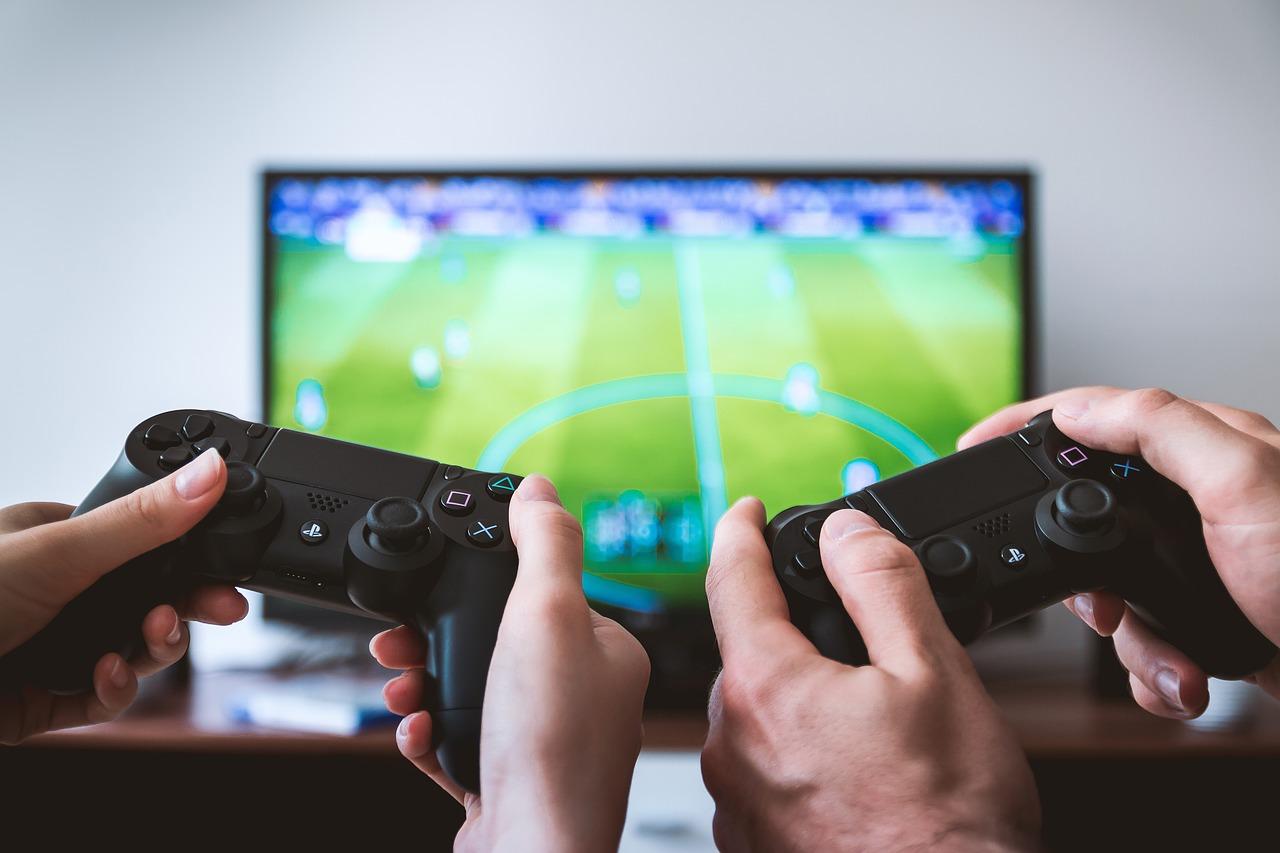 Två tv-spelskontroller framför ett fifa-spel