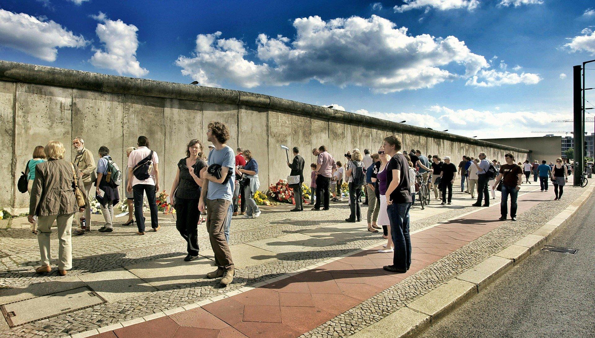 Människor går på gatan där muren står