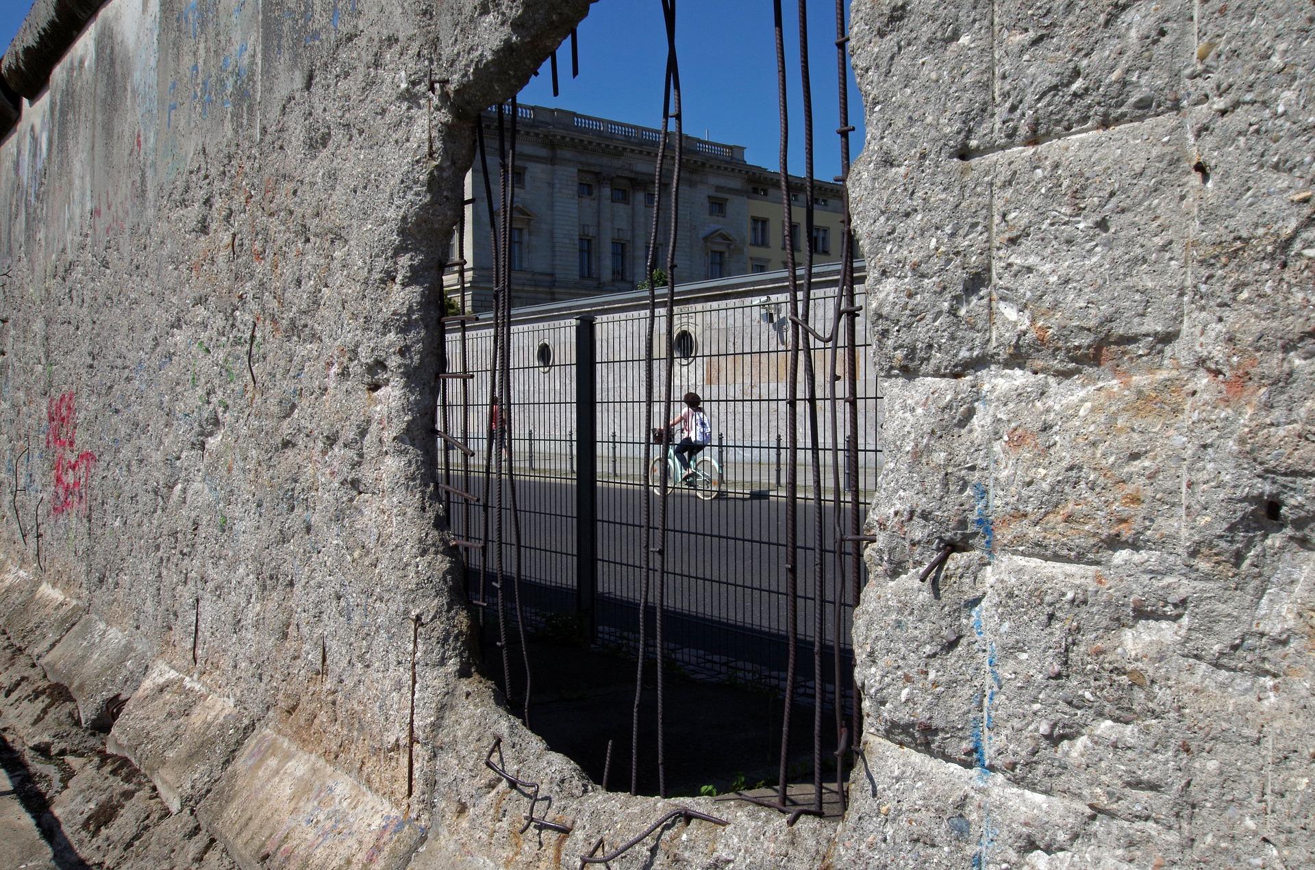Berlinmuren i betong med ett hål i den.