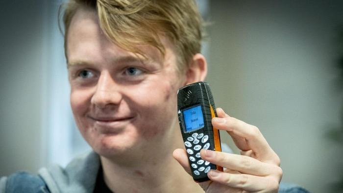 Simon håller upp en gammal mobiltelefon