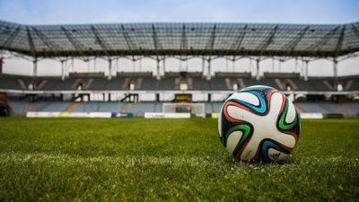 Foto på en fotboll på en stor fotbollsplan.