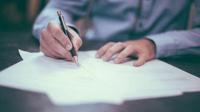 Foto på person som sitter och skriver.