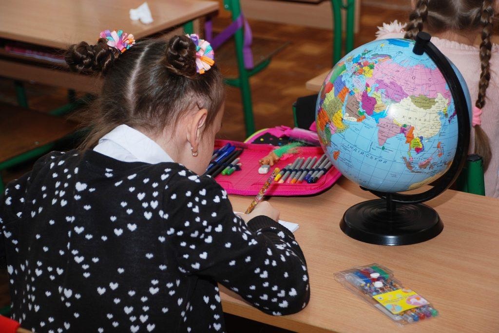 En elev sitter och skriver vid en skolbänk, bredvid eleven står en jordglob