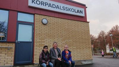 Annica, Mumen och Noah sitter på en bänk vid Korpadalsskolan.