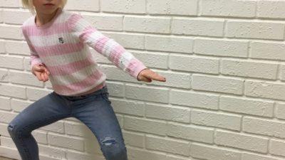 Ung tjej visar ett karateslag framför en vit tegelvägg.