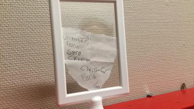 Ett foto på den handskrivna lappen som eleverna hittade. På lappen står det fem namn och årtalet 1998.