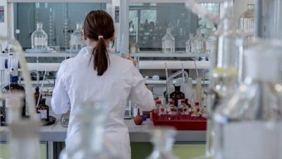 Foto på en kvinna i vit rock som står i ett sjukhuslaboratorium.