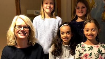 Foto på Malin Stehn tillsammans med eleverna som skrivit reportaget.