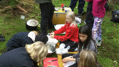 Eleverna sitter i skogen och förbereder sin mat.