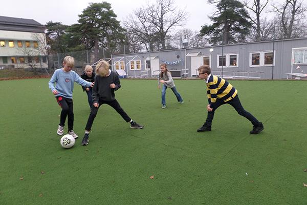 Foto på elever som spelar fotboll på skolans fotbollsplan.