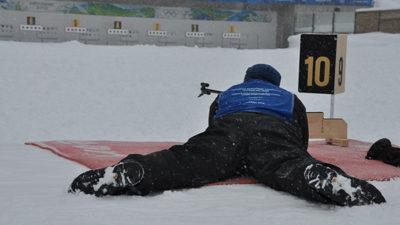 En skidåkare ligger beredd på att pricka tavlan i en tävling i skidskytte.