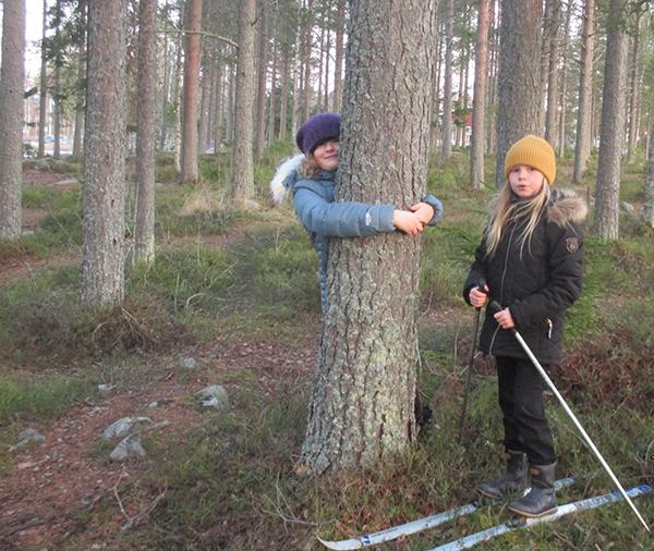 Två elever som står i skogen. Det är barmark. Men den ena flickan kramar ett träd, den andra tjejen har ett par skidor på sig.