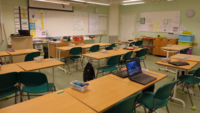Bänkar på rad i ett klassrum med lysrör i taket.