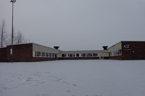 Foto på en röd skolbyggnad.
