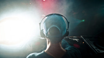 Foto på en person med keps och hörlurar som tittar ut över ett publikhav.