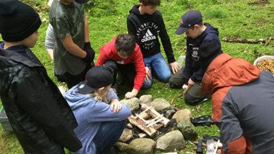 Foto på elever som sitter i mossan runt en lägereld som ännu ej har börjat brinna.
