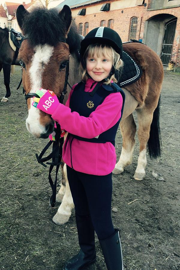 En ridtjej i rosa tröja klappar en brun häst på mulen.