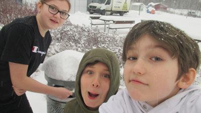Foto på tre elever framför en soptunna på en snöig skolgård.