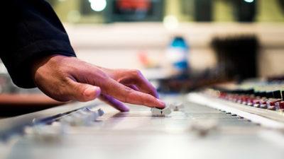 Närbild på händer som drar i spakar vid ett mixerbord.