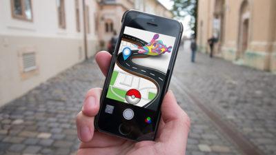 En mobiltelefon med Pokémon go i förgrunden och en gata i bakgrunden.