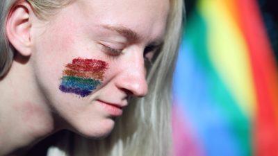 Tjej målad med regnbågsfärger på kinden.