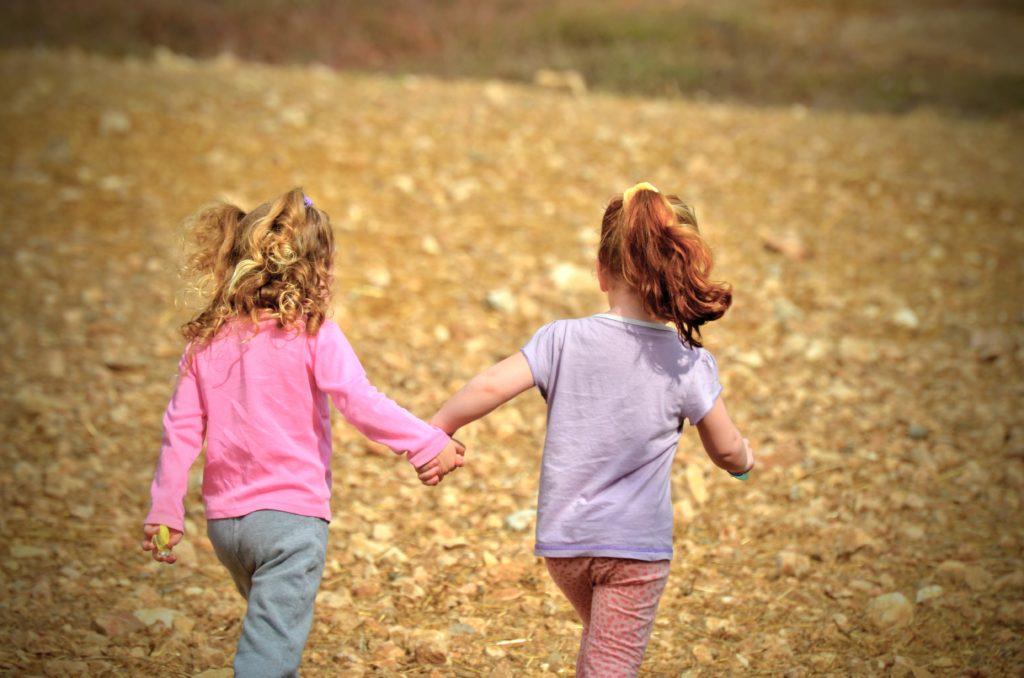 Två tjejer håller varandra i handen.