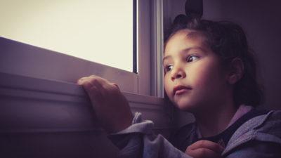 En flicka som är inomhus och tittar ut genom fönstret.