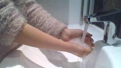 En elev som tvättar händerna under rinnande vatten.