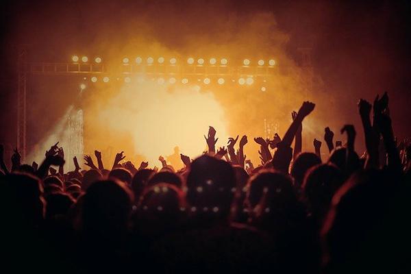 Foto från en konsert. Händerna i luften och ljus från scenen.