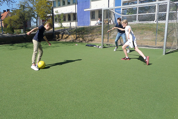 Tre elever som spelar fotboll.